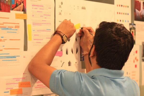 A picture of a person pinning up important things on a board.