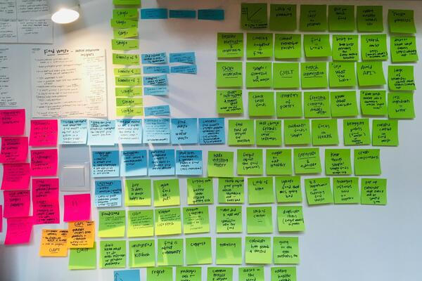 Photo by Hugo Rocha on Unsplash showing a lot of sticky notes while doing a scenario session